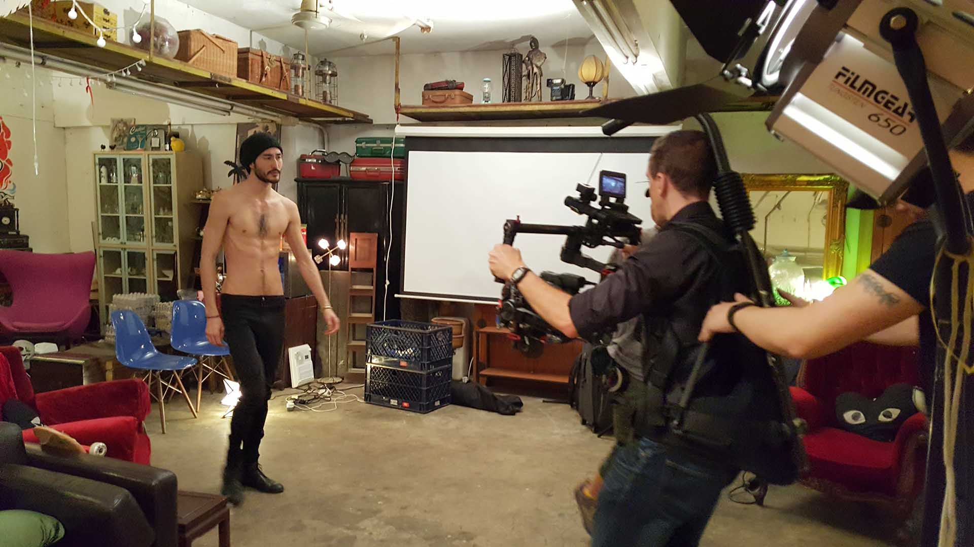 Behind the scenes shot of a cameraman using a Ronin to film a male model.