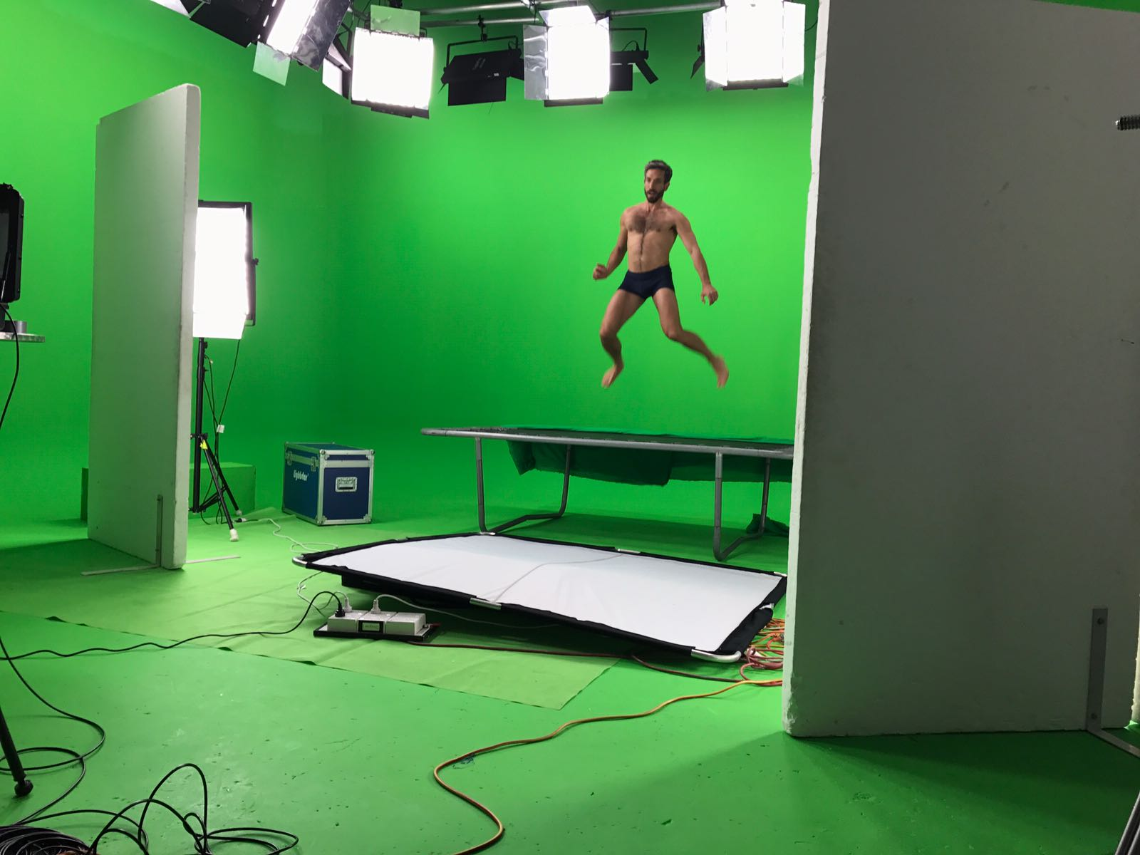 A male model jumping on a trampoline in a green screen studio.