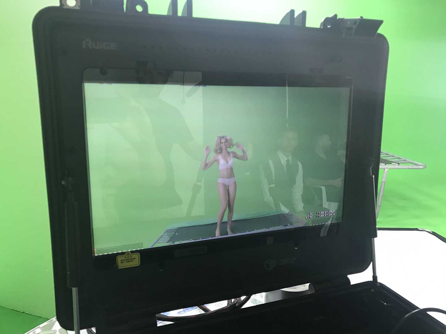 Through a monitor we see a female model on a trampoline in a green screen studio.
