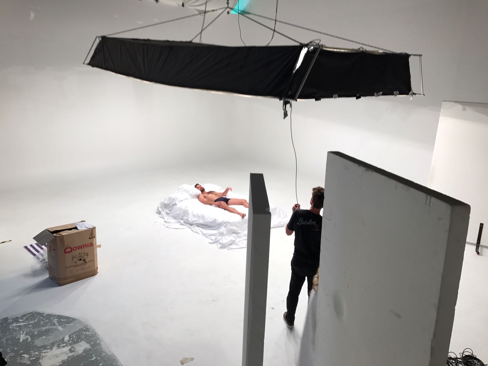 A male model lies on a white bed while being filmed in a studio.