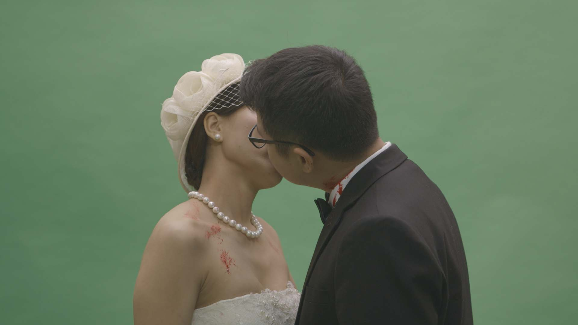 A bridge and groom kiss on green screen.