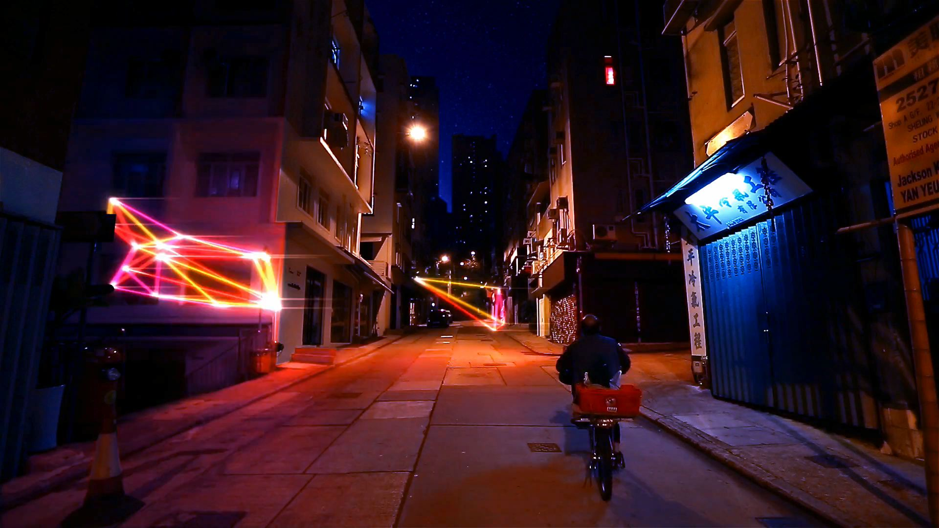 A man rides his bike through a Hong Kong street, animated shapes whiz by.