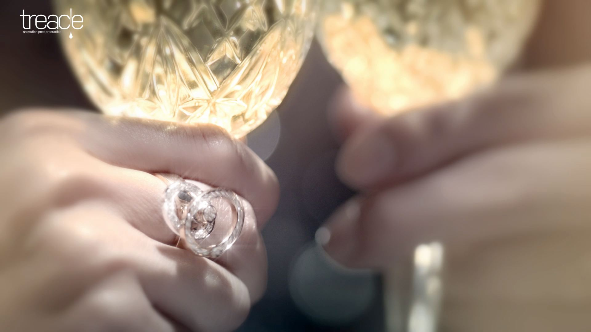 Close-up of a diamond ring on a woman's hand holding a champagne glass.