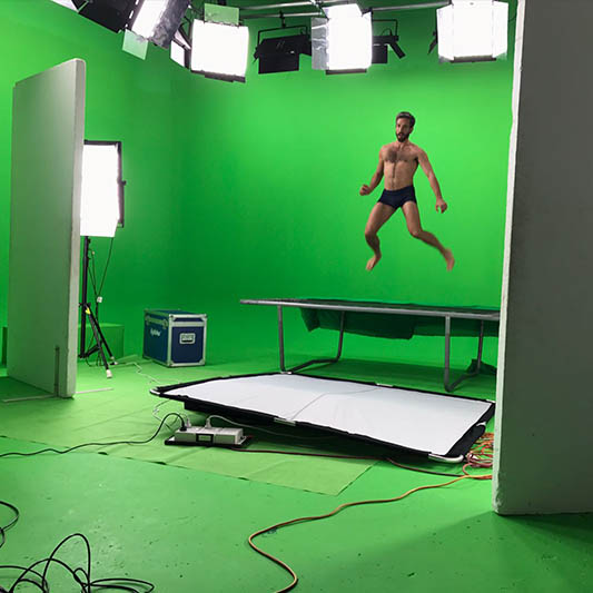 A male model jumping on a trampoline in a green-screen studio.