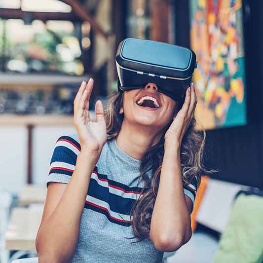 A smiley young woman using VR goggles
